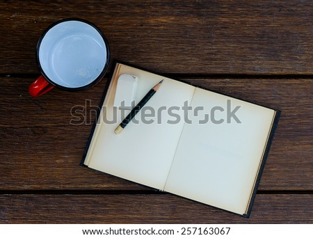 open blank old notebook on wooden table with empty red cup and rubber and pencil - stock photo