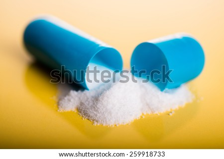 Open blue capsule pill with white powder drug on yellow background - stock photo