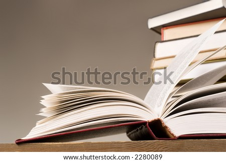 open book and a few books in stock on second plan - stock photo