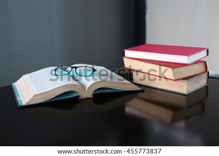 Open book and hardcover books on wooden table in library. Education background. - stock photo