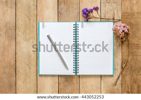 Open book and pen with dried flower on wooden background - stock photo