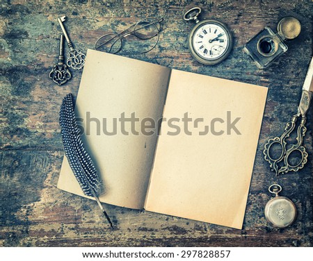 Open book and vintage writing on wooden table. Feather pen, inkwell, keys on textured background. Retro style toned picture with vignette - stock photo