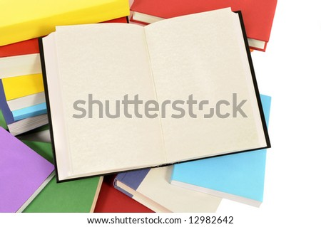Open book : blank book laying amongst a collection of colorful books.  Space for copy. - stock photo