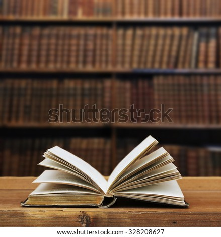 open book in front of an antique shelf. - stock photo