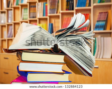 Open book lying on a stack of books - stock photo