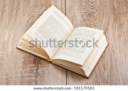 open book lying on a wooden table - stock photo