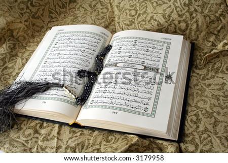 Open book of Holy koran & rosary - stock photo