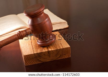 Open book of laws and gavel on the table - stock photo