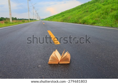 Open book on road outdoors - stock photo