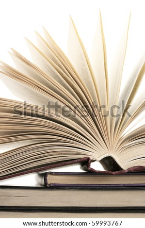 Open book on stack of books against white background. - stock photo