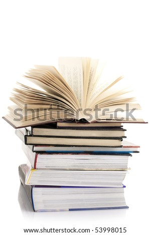Open book on stack of various books isolated on white background. - stock photo
