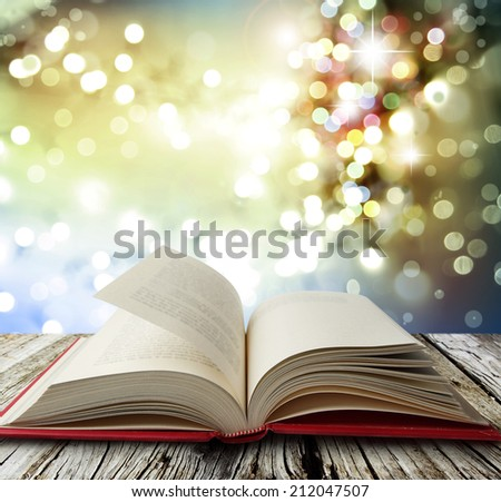 Open book on table in front of bright lights - stock photo