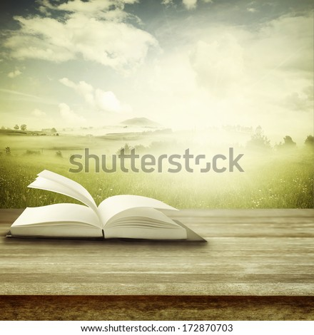 Open book on table in front of spring background - stock photo