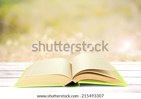 Open book on table outdoors - stock photo