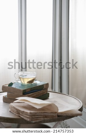 Open book on table with herbal tea in bedroom - stock photo