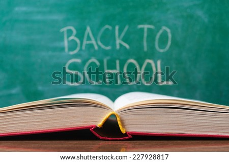 Open book on the desk and Back to School handwritten on the chalkboard - stock photo