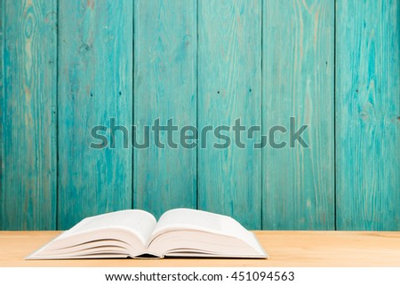 Open book on the desk over wooden background - stock photo