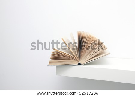 Open book on the shelf - stock photo