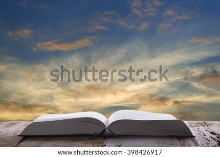 Open book on wood table and sunset as background - stock photo