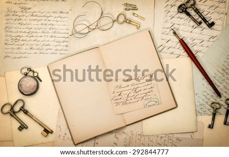 Open book, vintage accessories, old letters and postcards. Nostalgic paper background - stock photo