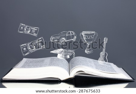 Open book with drawings on grey background - stock photo