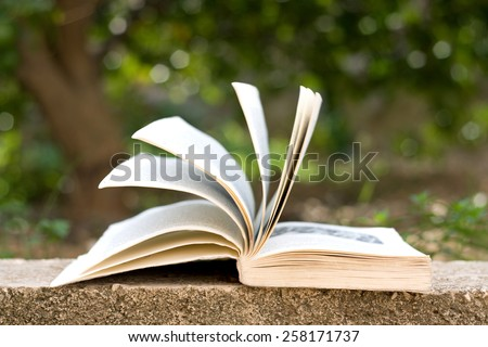 Open book with flipped pages, beautiful green bokeh. Selective focus.  - stock photo