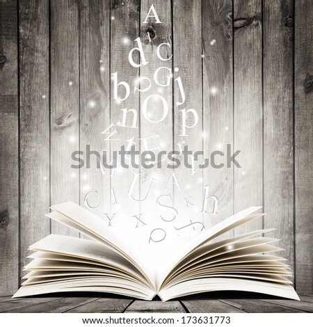 Open book with flying letters over wooden background. Magic book - stock photo