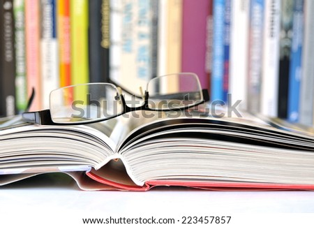 Open book with glasses, multicolored books in background - stock photo