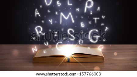 Open book with glowing letters flying out on wood deck - stock photo