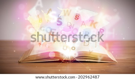Open book with glowing letters on concrete background. Colorful education concept - stock photo