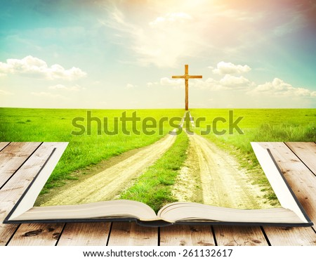 Open book with grass and a way walking towards a cross - stock photo