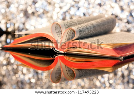 Open book with pages in the form of a heart on sparkly background - stock photo
