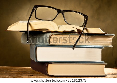 open book with reading glasses on the dark background - stock photo
