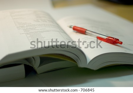 open book with red pen, soft focus - stock photo
