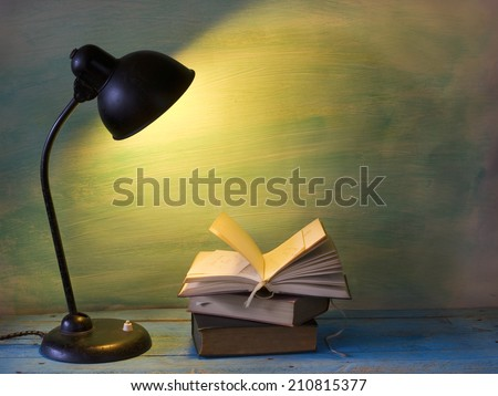 open book with vintage lamp, free copy space - stock photo