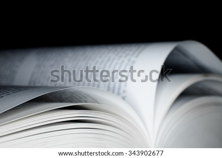 Open book with with shallow depth of field with black background - stock photo