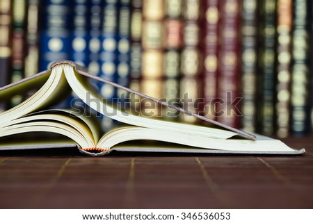 Open books with bookcase in the background - stock photo