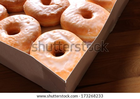 Open box of glazed doughnuts with a few missing - stock photo