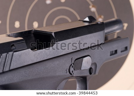 Open breech of a large 9mm pistol with target behind - stock photo