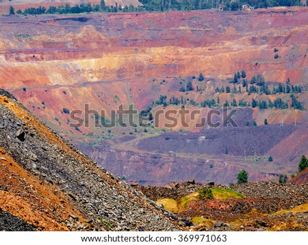 Open cast mine with colorful ore dump on the foreground - stock photo