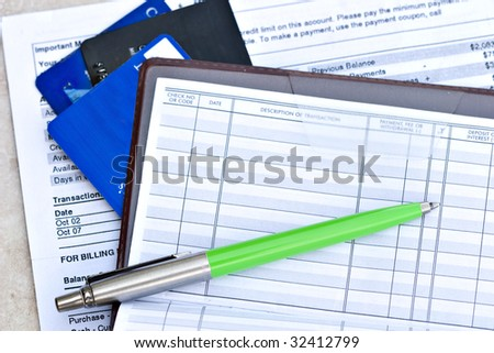 Open checkbook with credit cards and statement - stock photo