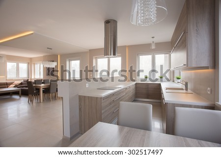 Open-concept cream beige wooden kitchen with dining space - stock photo
