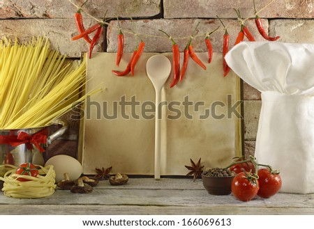 Open cook book with white toque and metal pot full of spaghetti - stock photo