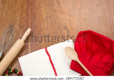 open cookbook, chef's hat and kitchen tools on wood table - stock photo