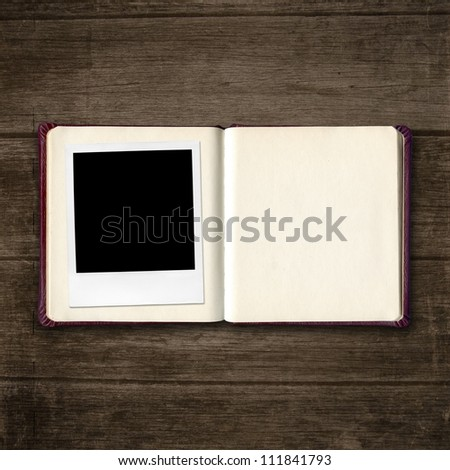 open diary book with photo frame on old wooden table - stock photo