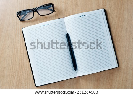 Open diary or office journal with a double page lined blank spread for your text with a ballpoint pen and glasses on a wooden desk, overhead view - stock photo