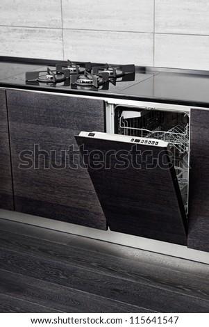 Open dish washer machine and gas-stove on black hardwood kitchen - stock photo