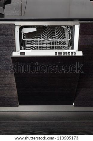 Open dish washer machine on black hardwood kitchen - stock photo