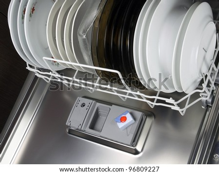open dishwasher with clean plates in it, focus on tabs dishwasher tabs - stock photo