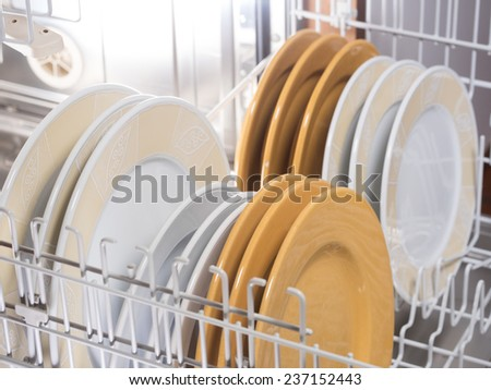 open dishwasher with different colored and sized plates - stock photo